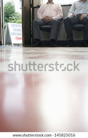 Low section of two male customers waiting in barber shop - stock photo