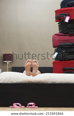 Low section of woman lying down in bed next to stack of suitcases - stock photo