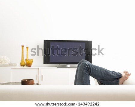 Low section of woman lying on sofa with television in contemporary living room - stock photo