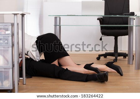 Low section of young business couple getting intimate on floor in office - stock photo