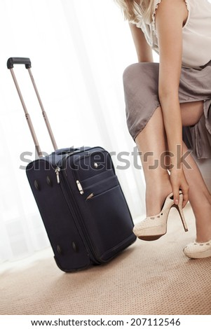 Low section of young businesswoman removing high heels in hotel room - stock photo