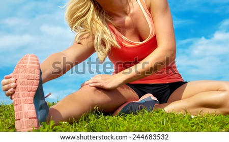 Low section of young female athlete stretching at park against sky - stock photo