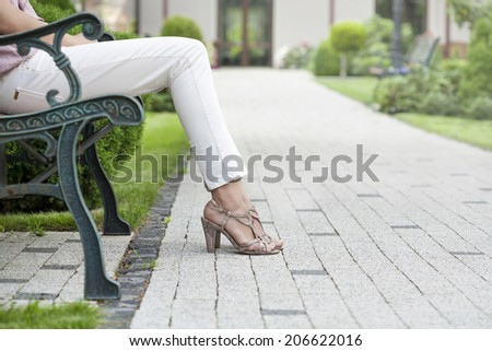 Low section of young woman sitting on park bench - stock photo