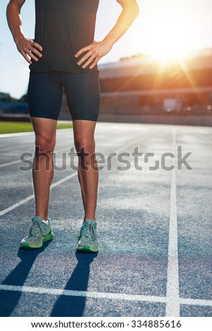 Low section shot of athlete man standing on race track with his hands on hips. Cropped shot of male runner on athletics running track in stadium on a sunny day. - stock photo
