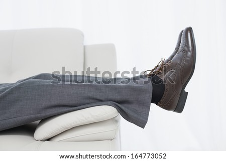 Low section side view of a businessman resting on sofa in the living room at home - stock photo