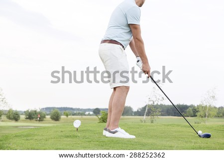 Low section side view of man playing golf against clear sky - stock photo