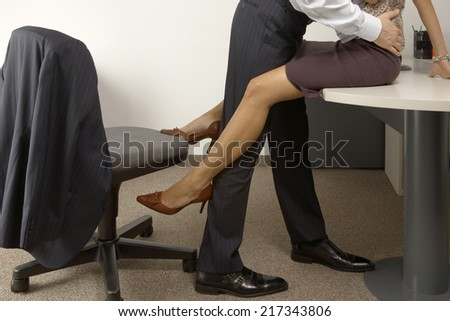 Low section view of a businessman and a businesswoman flirting in an office - stock photo