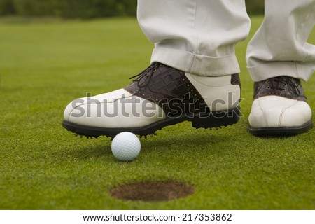 Low section view of a man putting a golf ball into a hole with a foot - stock photo