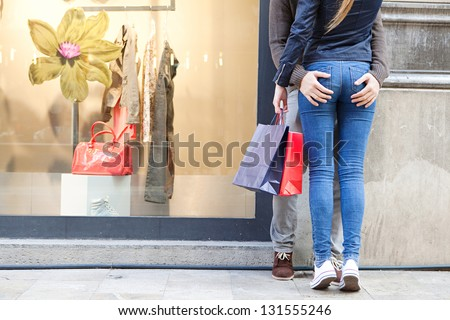 Low section view of a sexy young tourist couple shopping in the city and leaning on a wall hugging. - stock photo