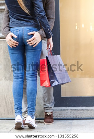Low section view of a sexy young tourist couple shopping in the city and leaning on a wall hugging.