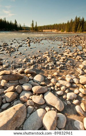 Low shot of golden sun rays shining over pebbles at river bank. - stock photo