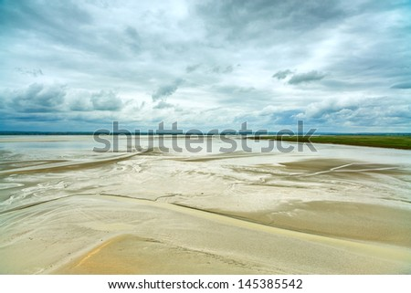 Low tide and monastery detail in Mont Saint Michel Bay landmark. Tourists cross the bay. Normandy, France, Europe - stock photo