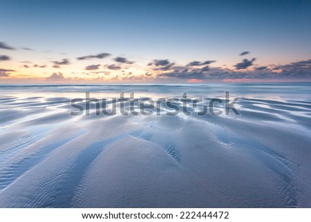 Low tide at sunset - stock photo