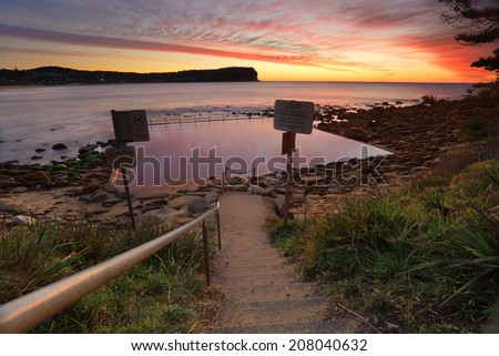 Low tide exposes the rocky end of Macmasters Beach where the tidal pool is calm reflecting pretty patterns in the sunrise sky - stock photo