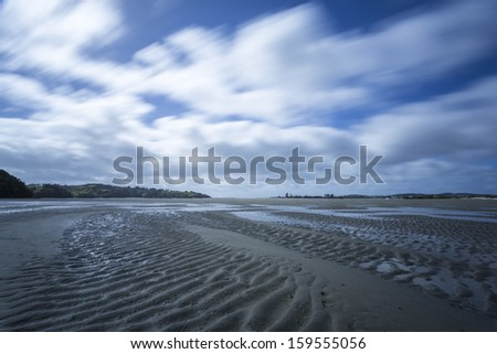 low tide/ tidal estuary mudflats at low tide with the sand exposed  - stock photo