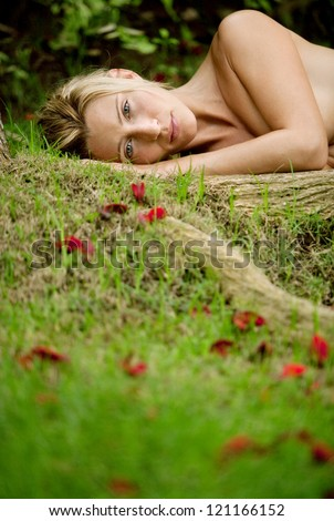 Low view of a beautiful blonde woman laying naked on green grass and tree roots, covered in red rose petals. - stock photo