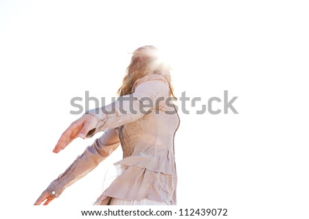 Low view of a young girl enjoying the sun with her arms open against the sky. - stock photo