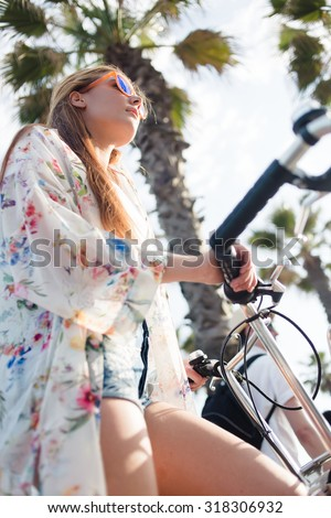 Low view of beautiful funky woman standing with her vintage bike on the street against tropical sky in summer day, charming female dressed in stylish clothes walking with  bicycle during weekend - stock photo