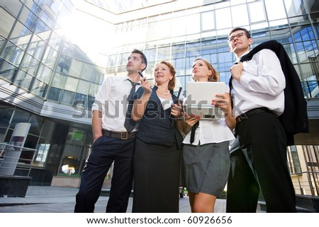 Low view of group of office workers staying outdoors after hard working day. People holding laptop computer and thinking about new business projects concerning office building. - stock photo