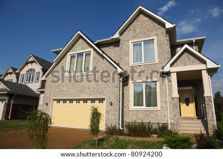 Low view of new two-storied beige stone cottage with yellow garage and brown roof. - stock photo