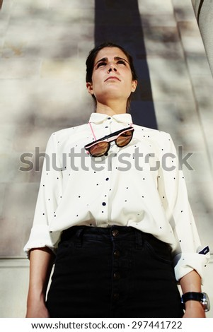 Low view portrait of glamorous young teenager girl with modern clothes and fashionable sunglasses looking straight on sunny summer afternoon outdoors, hipster woman with serious face look in distance - stock photo
