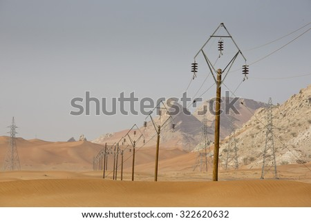 Low voltage electric power transmission lines with pylons or poles as part of power grid in red sand desert landscape scene with sand dunes in United Arab Emirates, Arabia, with blue sky - stock photo