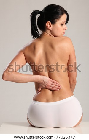 Lower back pain and ache for beautiful young woman wearing white knickers with a naked back. - stock photo