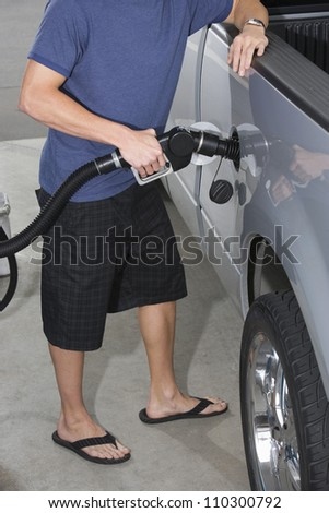 Lower body of a young man refueling his car - stock photo
