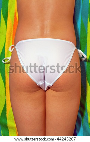 Lower half of a woman sunbathing wearing white bikini bottoms