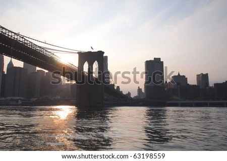 Lower Manhattan and Brooklyn bridge at sunset - stock photo
