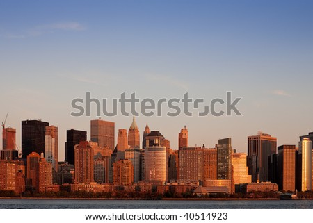 Lower Manhattan skyline bathed in the setting sun - stock photo