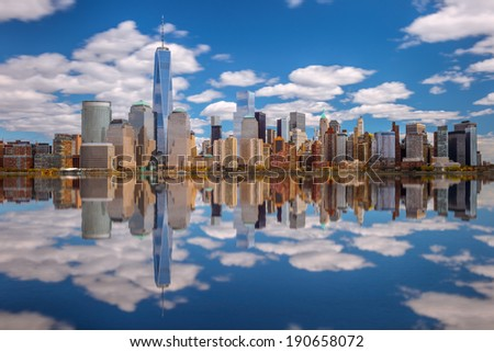 Lower Manhattan skyline panorama over East River with reflection and blue sky - stock photo