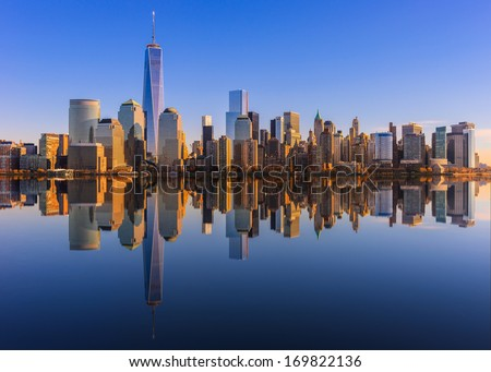 Lower Manhattan skyline panorama over East River with reflection at sunset - stock photo