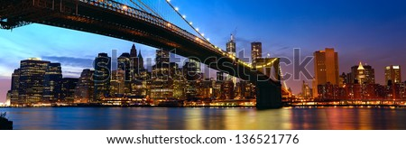 Lower Manhattan skyline panorama with Brooklyn Bridge at sunset in New York City