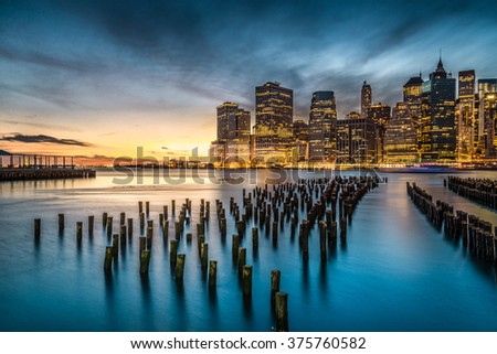 Lower Manhattan with sunset view from Brooklyn Bridge Park in New York City.