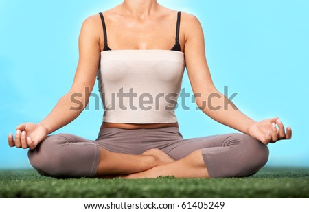Lower part of slim female meditating in pose of lotus in isolation - stock photo