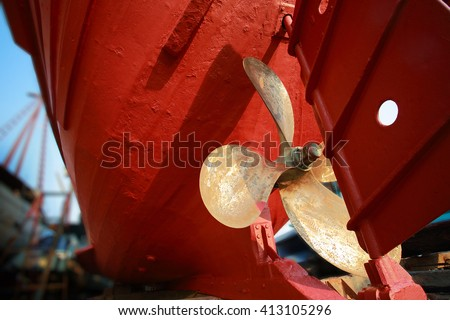 Lower part of stern and propeller of a fishing boat in a shipyard for maintenance.