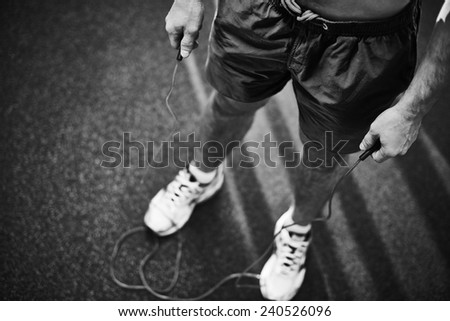 Lower part young man holding skipping rope - stock photo