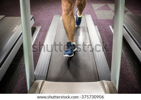 Lower section of man running on treadmill at the gym - stock photo