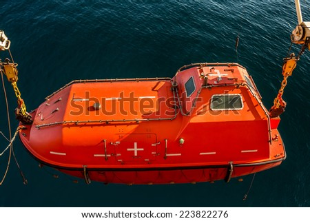 Lowered orange lifeboat with a sea background - stock photo