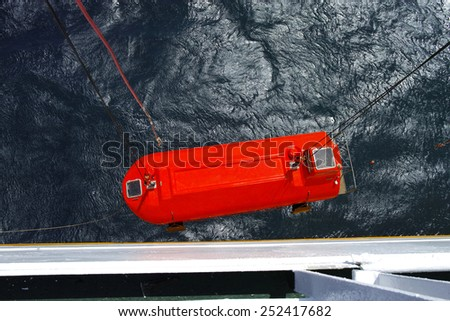 lowering of a lifeboat during a drill on a ship - stock photo