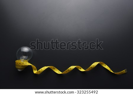 Lowlight key of light bulb and Yellow measuring tape with water drop on grey background - stock photo