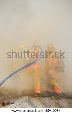 Lt Martin and FF Sullivan working an active attic fire in a Single family dwelling on fire on SE Mill Street in the Mill Pine Historic District of Roseburg Oregon. - stock photo