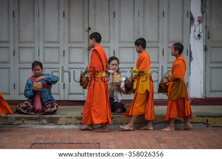 Luang Prabang, Laos - December 21, 2015: Novice monks are walking to collect alms and offerings in the world heritage site, Luang Prabang, Laos. - stock photo