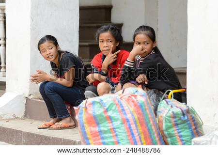 LUANG PRABANG, LAOS - SEP 25, 2014: Unidentified Lao girls at the porch. 55% of Laos people belong to the Lao ethnic group