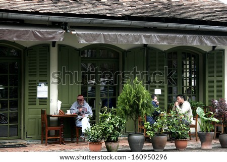 LUANGPRABANG, LAOS-JANUARY 2008: Unidentified Loas Coffee corner in Louangphabang. Tourist and Laos people sit out of coffee shop on footpath. Laos is Country in AEC. - stock photo