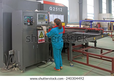 LUANNAN COUNTY - AUGUST 23: Women workers busy operating CNC machine in a production line, on august 23, 2014, Luannan County, Hebei Province, China   - stock photo