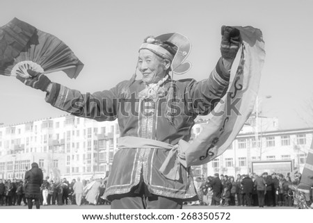 LUANNAN COUNTY - FEBRUARY 10:  Old woman wearing colorful clothes, performing yangko dance in the street, during the Chinese Lunar New Year, February 10, 2014, Luannan County, Hebei Province, China.  - stock photo