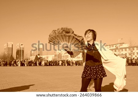 LUANNAN COUNTY - FEBRUARY 10: People wearing colorful clothes, performing yangko dance in the street, during the Chinese Lunar New Year, February 10, 2014, Luannan County, Hebei Province, China.  - stock photo