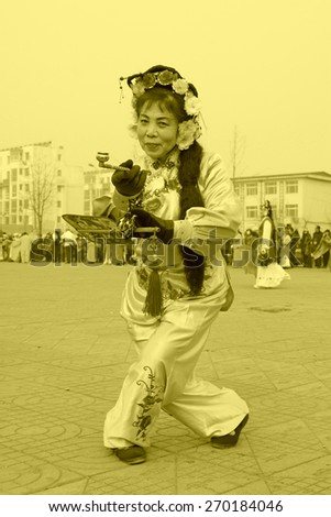 LUANNAN COUNTY - FEBRUARY 15: Woman holding pairs of wooden stick performing yangko dance in the street, during the Chinese Lunar New Year, February 15, 2014, Luannan County, Hebei Province, China. - stock photo